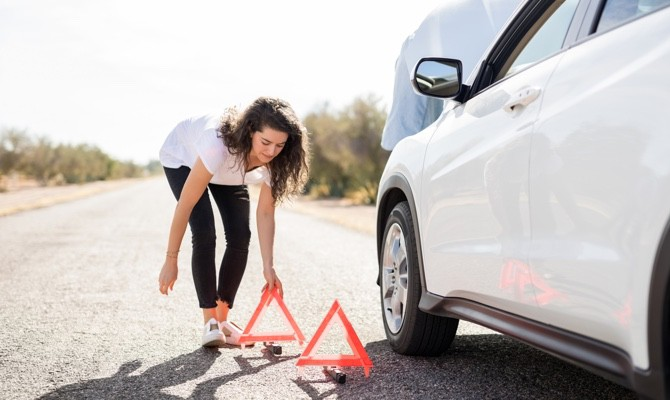 Champion-Woman-Placing-Triangles-Near-Car-Breakdown