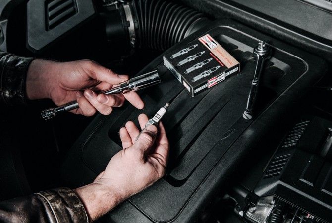 A hand holding a spark plug and a tool