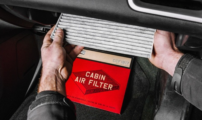 Mechanic replacing a cabin air filter with a new Champion cabin air filter.